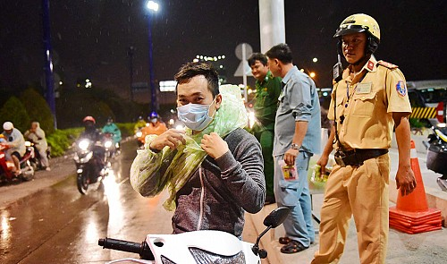 Saigon police hand out free wet weather ponchos to commuters