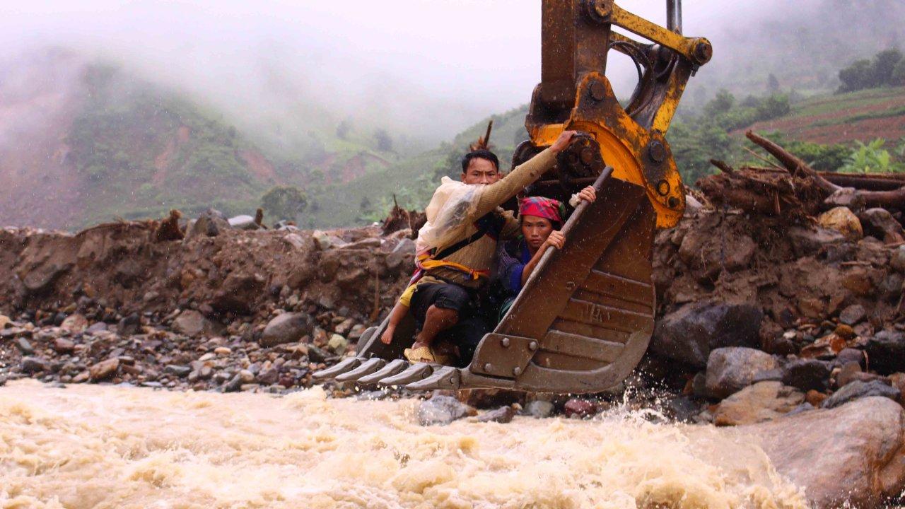 In Vietnam, excavator bucket ferries stranded villagers over swollen stream