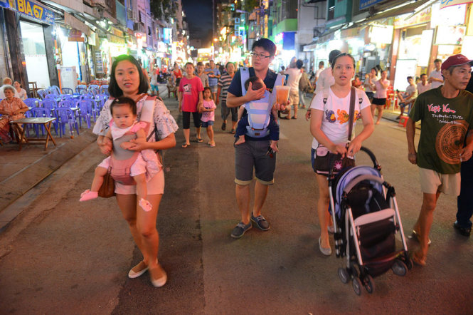 Visitors leisurely walk along Bui Vien.