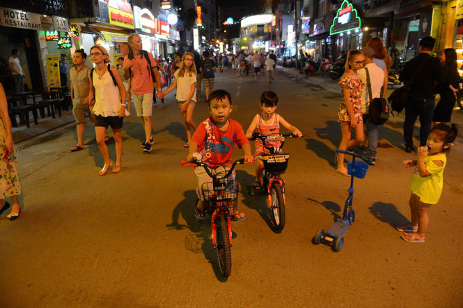 Children ride bicycle on Bui Vien.