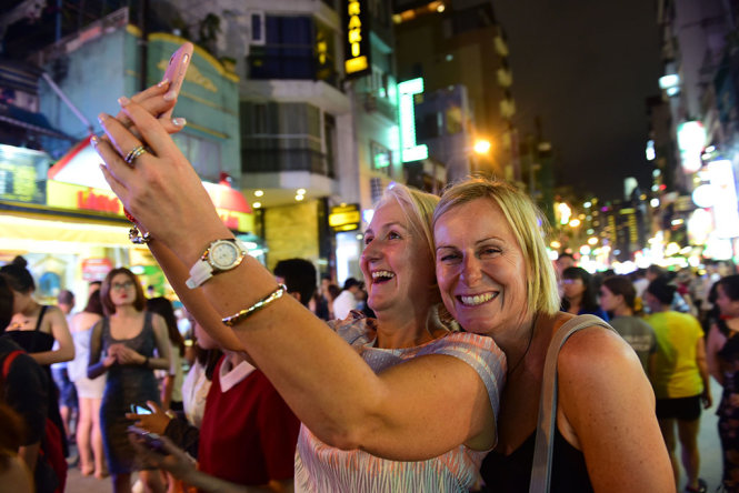 Two foreign tourists take a selfie at Bui Vien Walking Street.