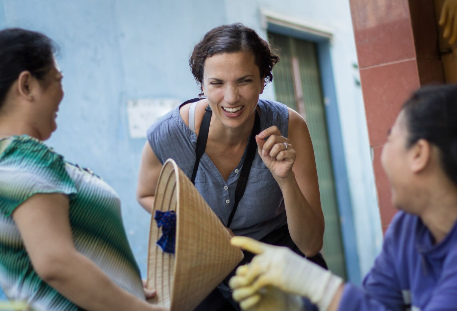 Tanya Olander laughing with two local vendors in a photo taken by photographer Maria Graven while the two were shooting in District 3 – Photo provided by Tanya Olander