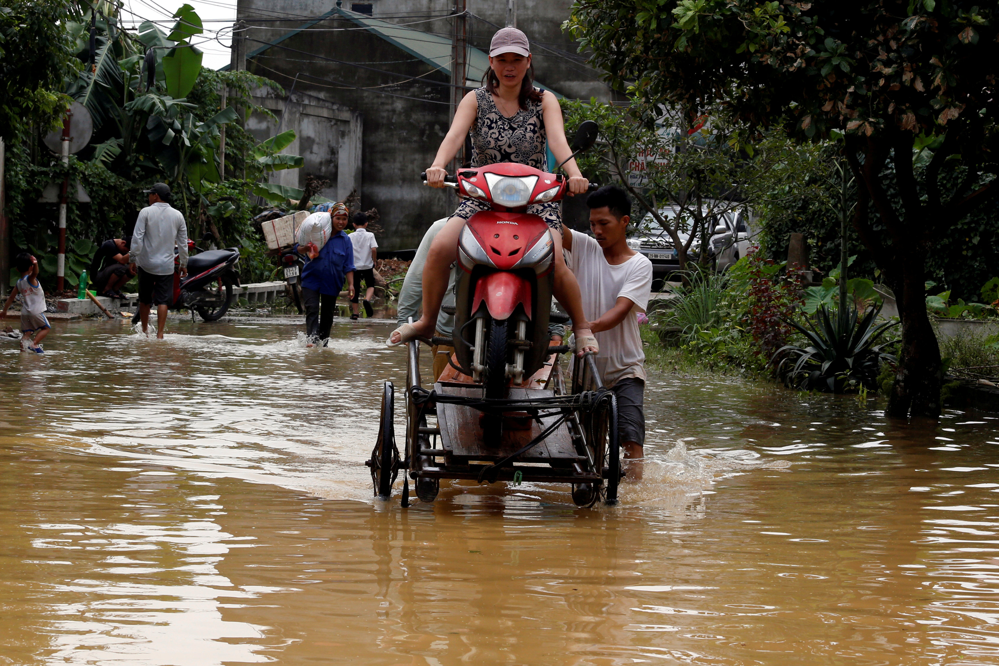 Men evacuate a woman through a flooded road after a tropical depression in Hanoi, Vietnam October 13, 2017. Photo: Reuters