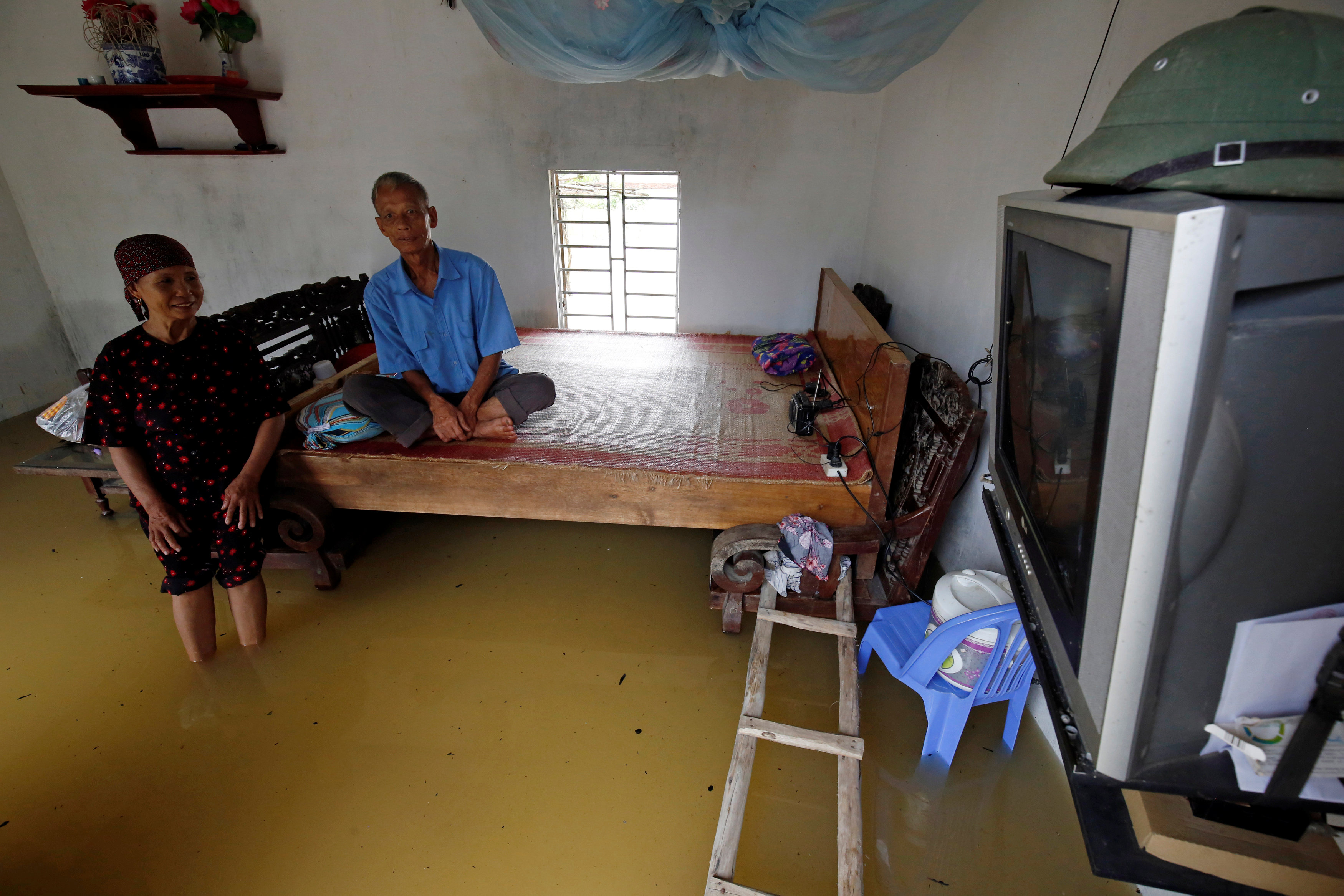 A couple watches TV in their flooded house after a tropical depression in Hanoi, Vietnam October 13, 2017. Photo: Reuters