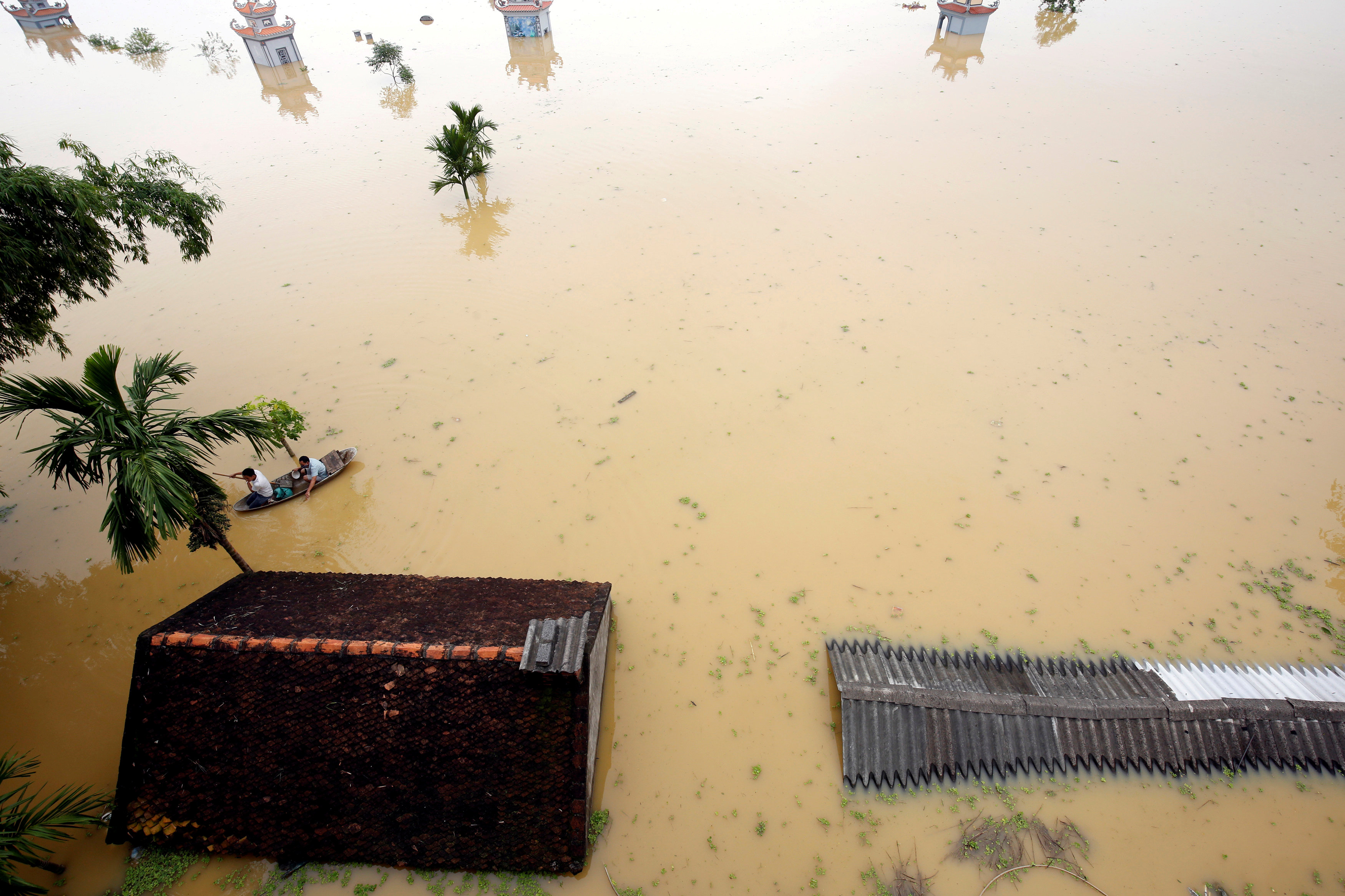 Farmers paddle in a boat at a flooded village after a tropical depression in Hanoi, Vietnam October 13, 2017. Photo: Reuters