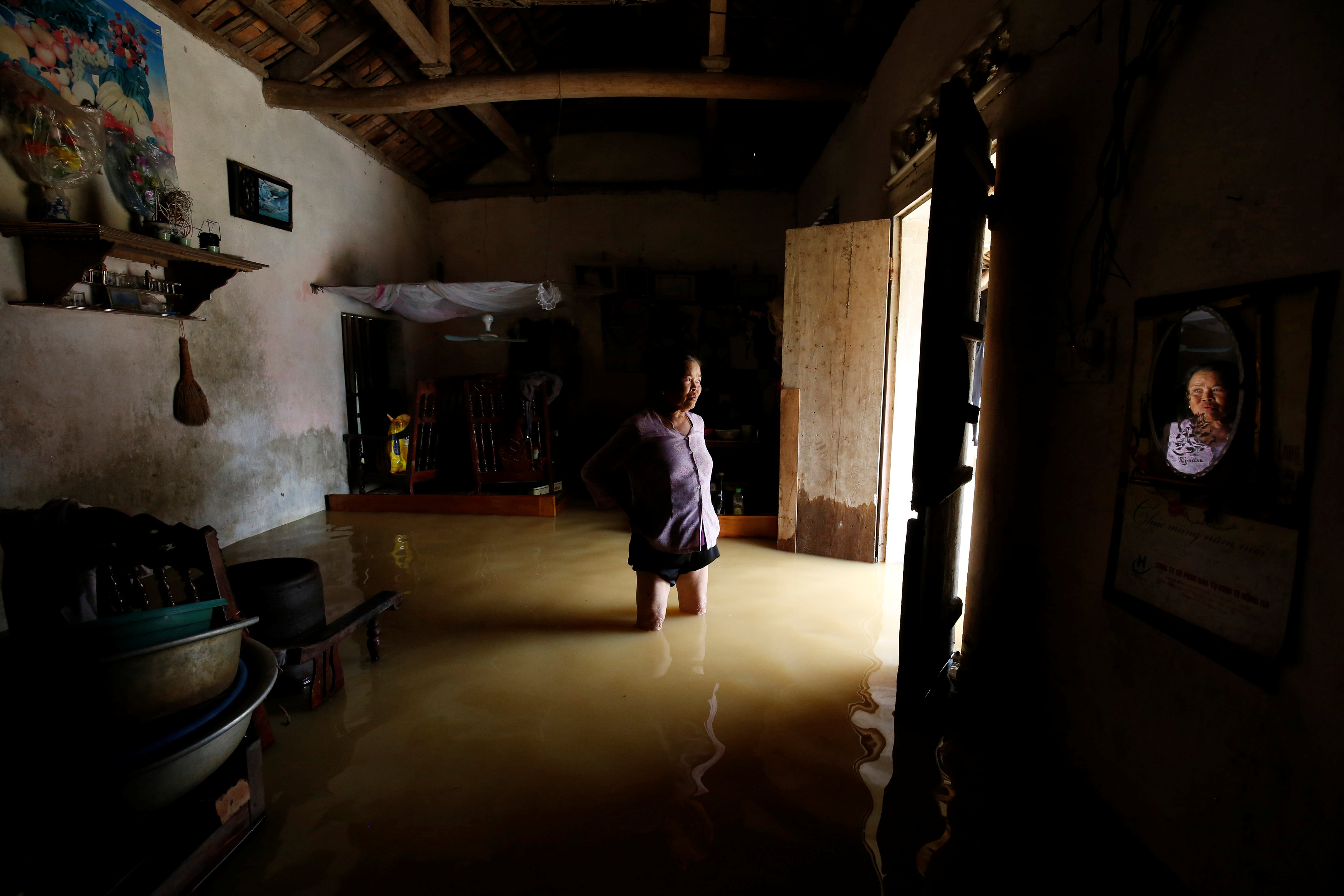 A farmer stands in her flooded house after a tropical depression in Hanoi, Vietnam October 13, 2017. Photo: Reuters