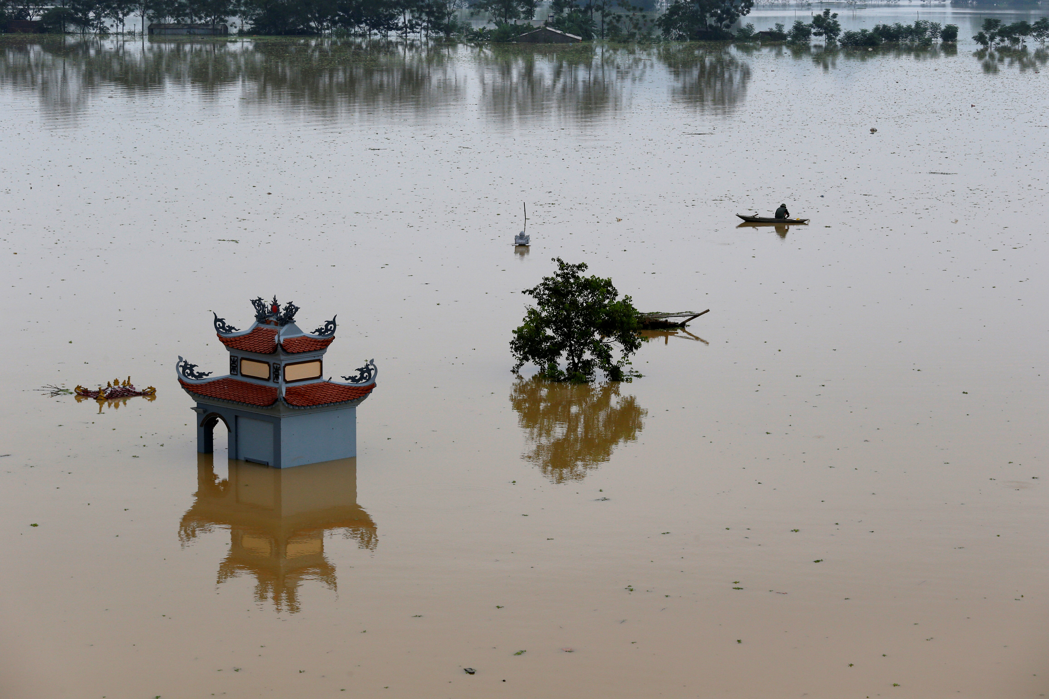 A farmer catches fish in a flooded village after a tropical depression in Hanoi, Vietnam October 13, 2017. Photo: Reuters