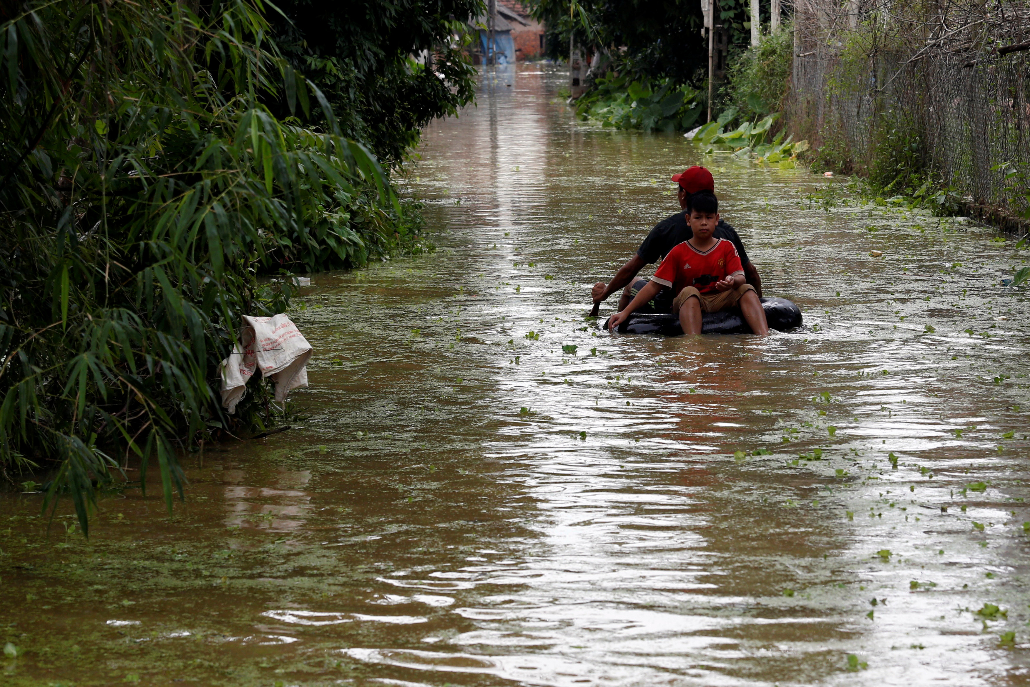 Boys paddle an improvised boat in a flooded village after a tropical depression in Hanoi, Vietnam October 13, 2017. Photo: Reuters