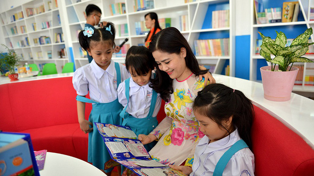 A teacher and her students are pictured reading in the improved library at Phan Van Tri Elementary School in District 1, Ho Chi Minh City. Photo: Tuoi Tre