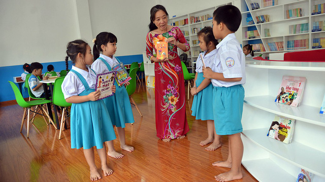 A teacher introducing a new book to students. Photo: Tuoi Tre