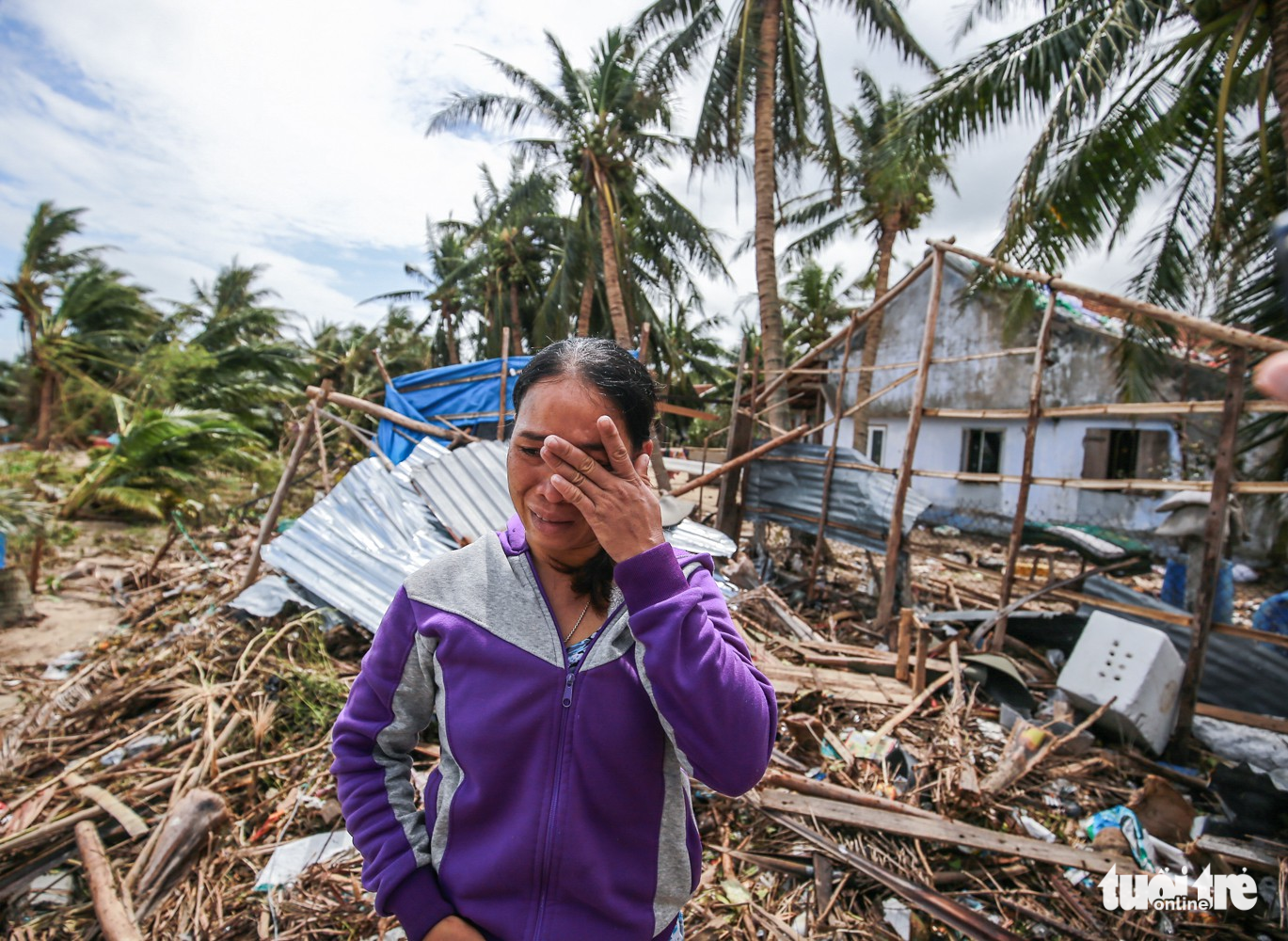 Phan Thi Bo, a resident of Van Phuoc Commune, wipes the tears from her face. Her home and fishing equipment were destroyed by storm Damrey.