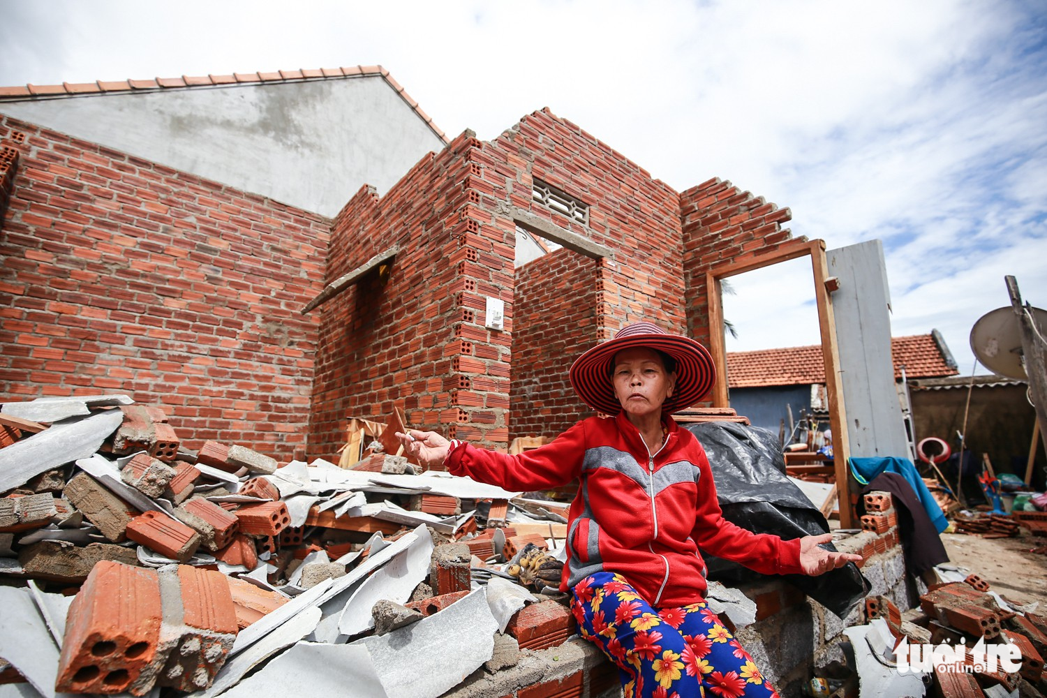 Phan Thi Lac, 63, sits by the debris of her home in Van Phuoc Commune.
