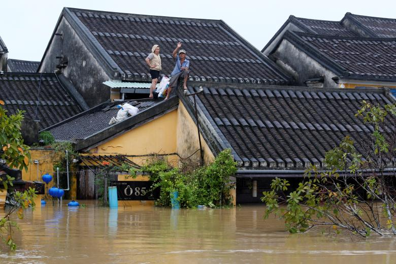 People stand on the roof of their house along submerged street in the UNESCO heritage ancient town of Hoi An after Typhoon Damrey hits Vietnam. Photo: Reuters