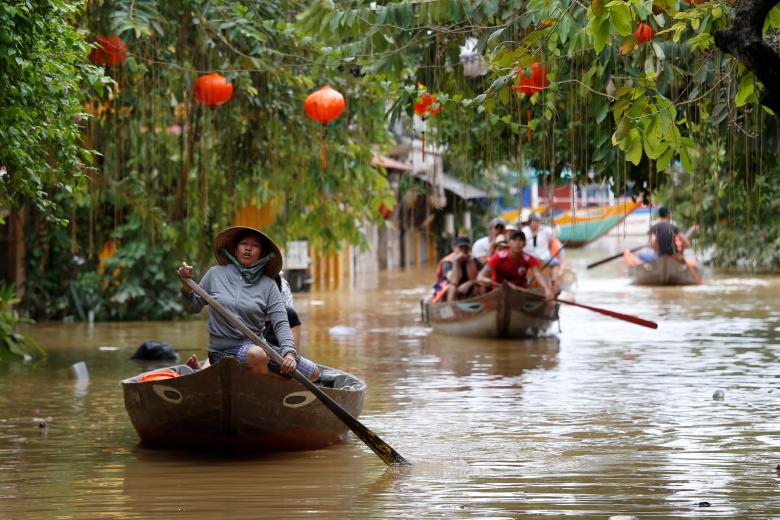 People ride boats past houses submerged by Typhoon Damrey in the UNESCO heritage ancient town of Hoi An, Vietnam. Photo: Reuters