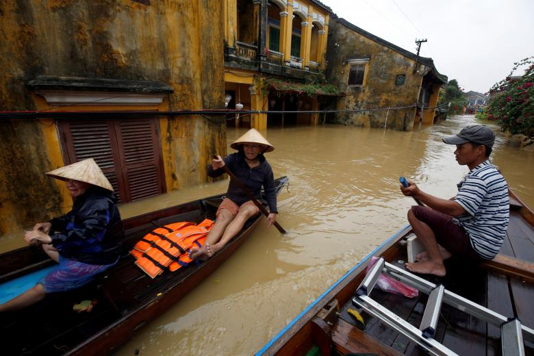 People ride a boat along submerged houses in the UNESCO heritage ancient town of Hoi An after Typhoon Damrey hits Vietnam. Photo: Reuters
