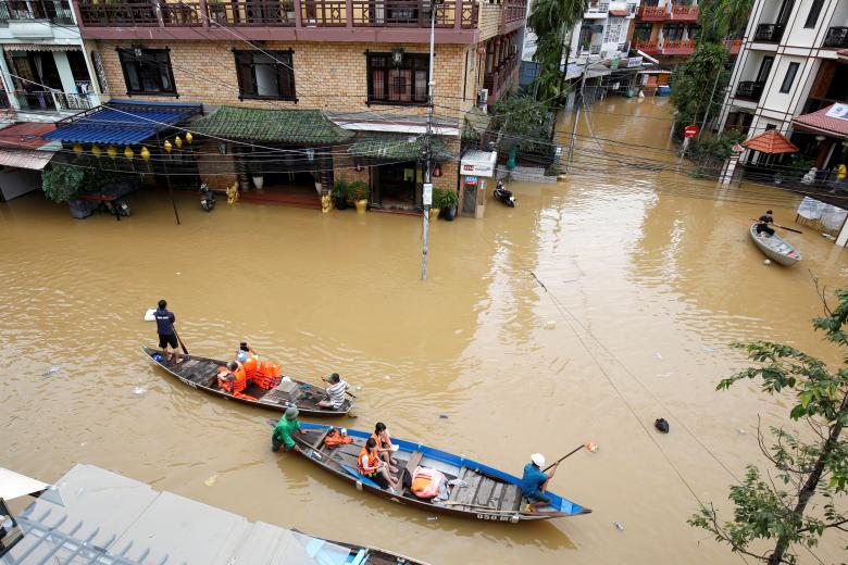 People travel on a boat along submerged by Typhoon Damrey houses in the UNESCO heritage ancient town of Hoi An, Vietnam. Photo: Reuters