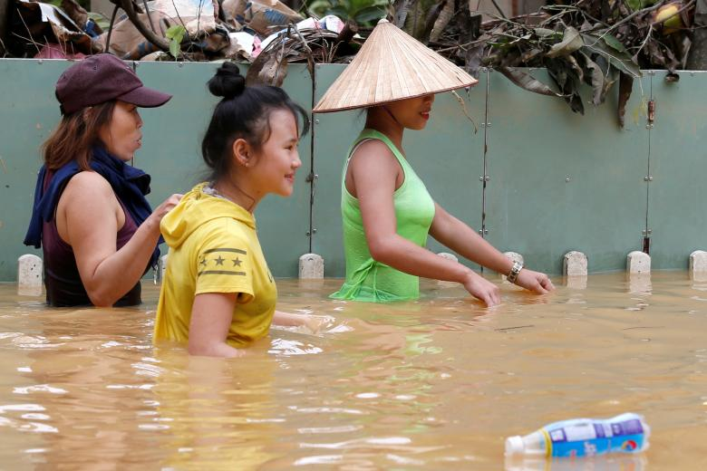 Women wade along submerged by Typhoon Damrey houses in the UNESCO heritage ancient town of Hoi An, Vietnam. Photo: Reuters