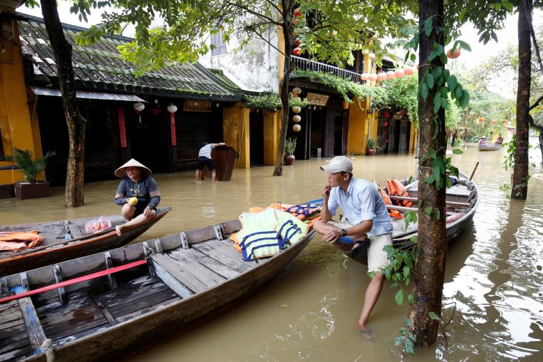 People sit on a boat at a flooded by Typhoon Damrey street in the UNESCO heritage ancient town of Hoi An, Vietnam. Photo: Reuters