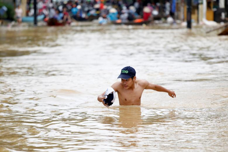A man wades along a flooded by Typhoon Damrey street in the UNESCO heritage ancient town of Hoi An, Vietnam. Photo: Reuters