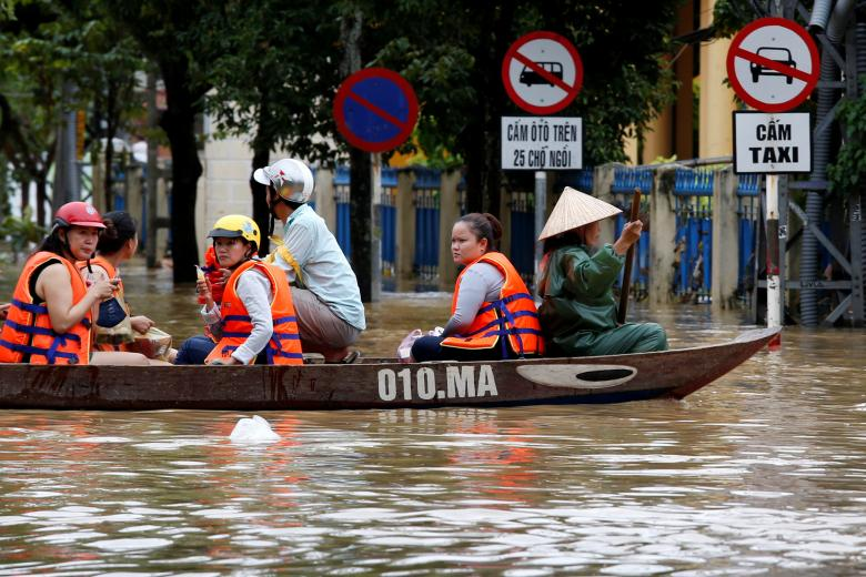 People ride a boat along a flooded by Typhoon Damrey street in the UNESCO heritage ancient town of Hoi An, Vietnam. Photo: Reuters