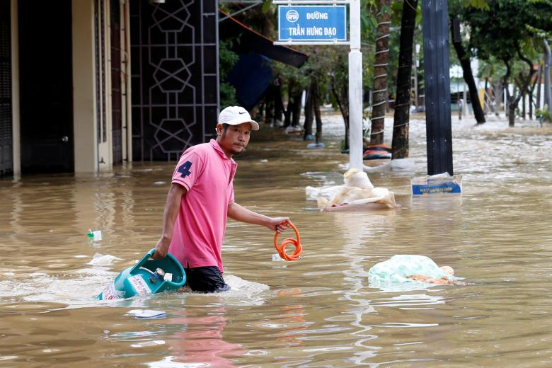 A man wades with a gas tank along submerged by Typhoon Damrey houses in the UNESCO heritage ancient town of Hoi An, Vietnam. Photo: Reuters