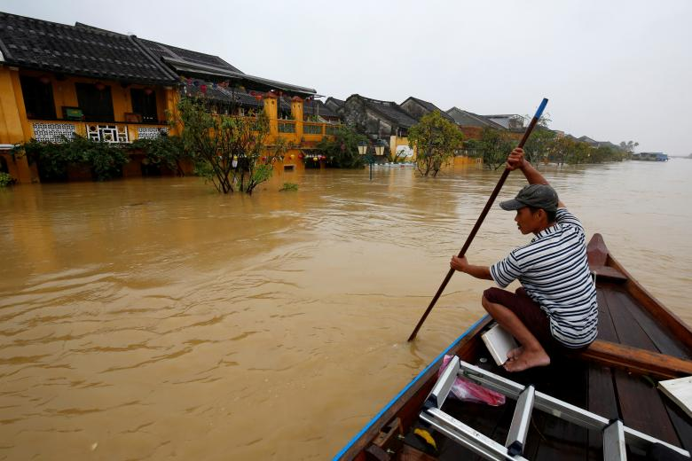 A man rides a boat along the overflowing Thu Bon river in the UNESCO heritage ancient town of Hoi An after Typhoon Damrey hits Vietnam. Photo: Reuters
