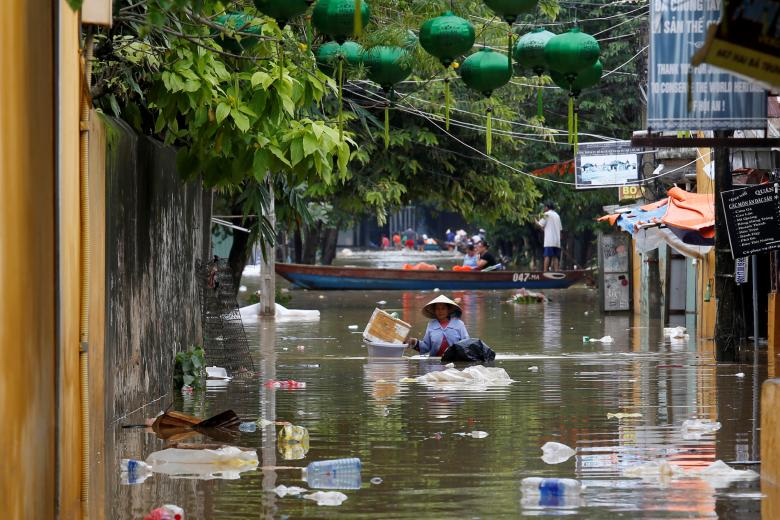 A woman wades along submerged by Typhoon Damrey houses in the UNESCO heritage ancient town of Hoi An, Vietnam. Photo: Reuters
