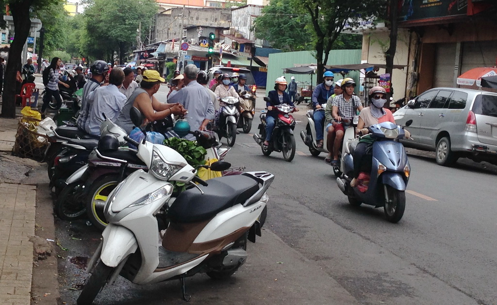 Bikes are parked along the street with riders sitting on them. Photo: Tuoi Tre