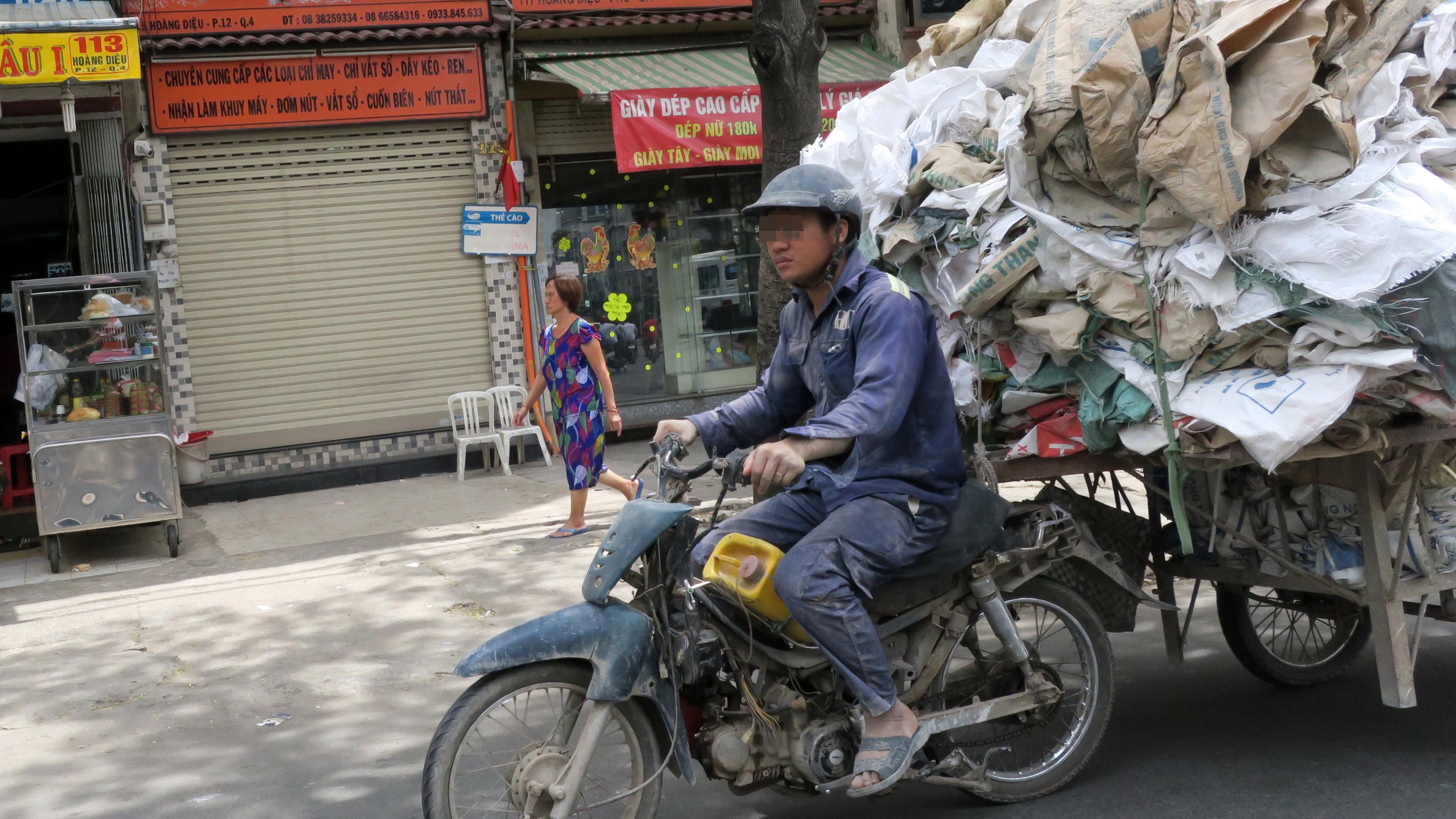 A man rides a ramshackle motorbike pulling bags on a cart as part of his daily job. Photo: Tuoi Tre