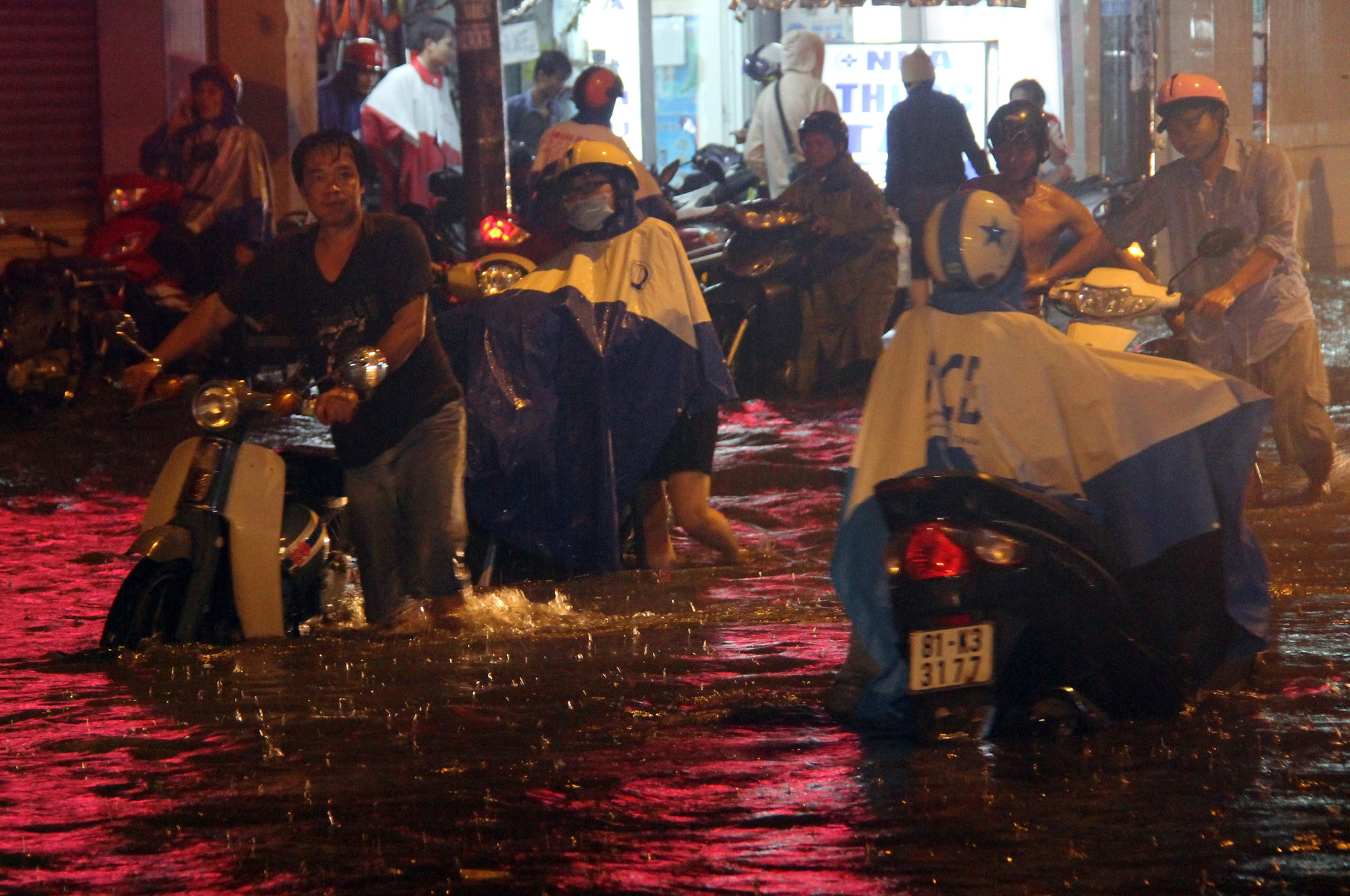 Riders have to walk their bikes through knee-deep water in Ho Chi Minh City. Photo: Tuoi Tre