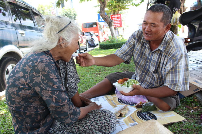 Nguyen Hung (R), 43, feeds his 81-year-old mother, in Da Nang, central Vietnam. Photo: Tuoi Tre