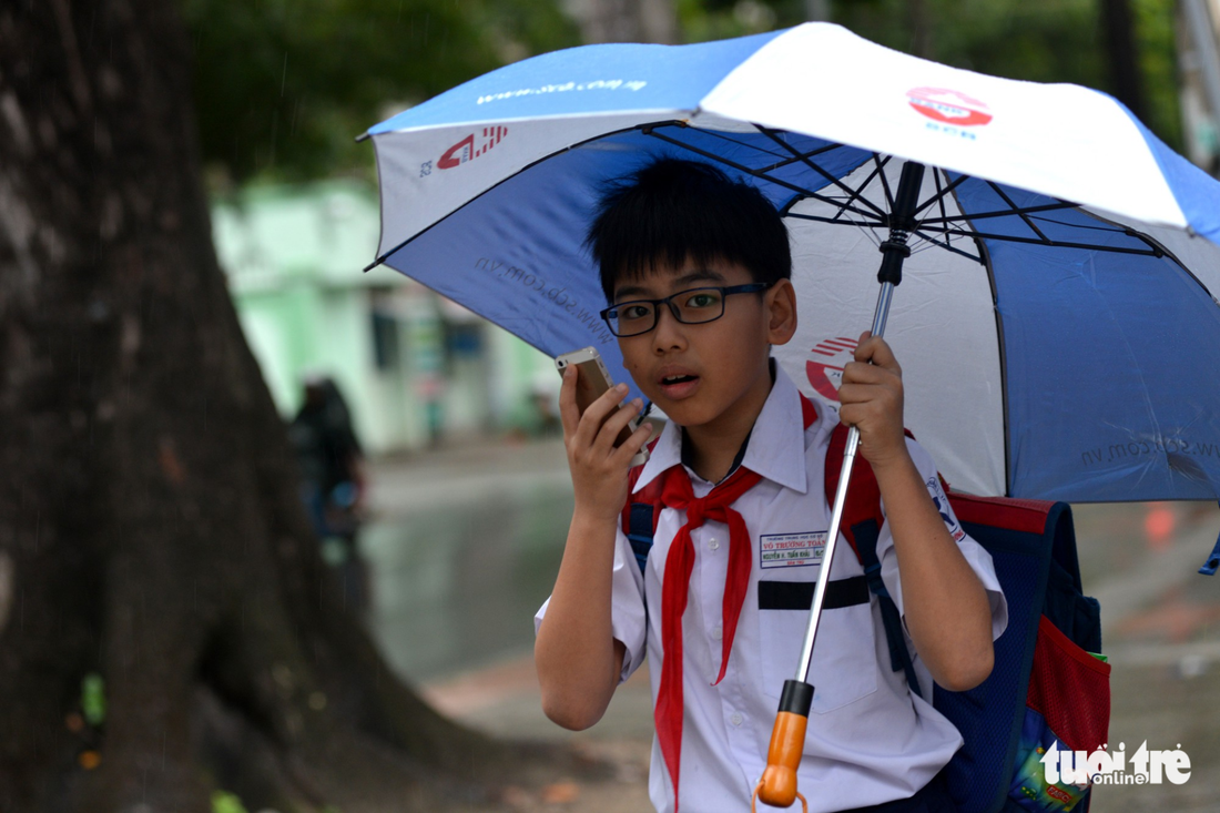 A sixth-grader calls his parents to pick him up early in Ho Chi Minh City on December 25, 2017. Photo: Tuoi Tre