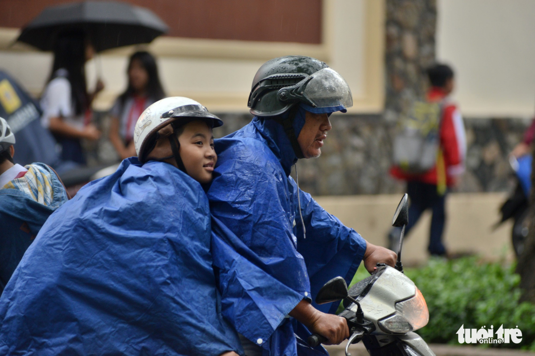 A father takes his son home in the rain in Ho Chi Minh City on December 25, 2017. Photo: Tuoi Tre