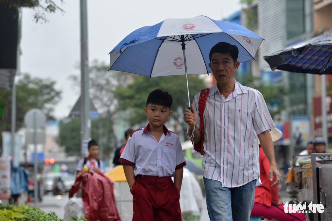 A man walks his son to school in the rain in Ho Chi Minh City on December 25, 2017. Photo: Tuoi Tre