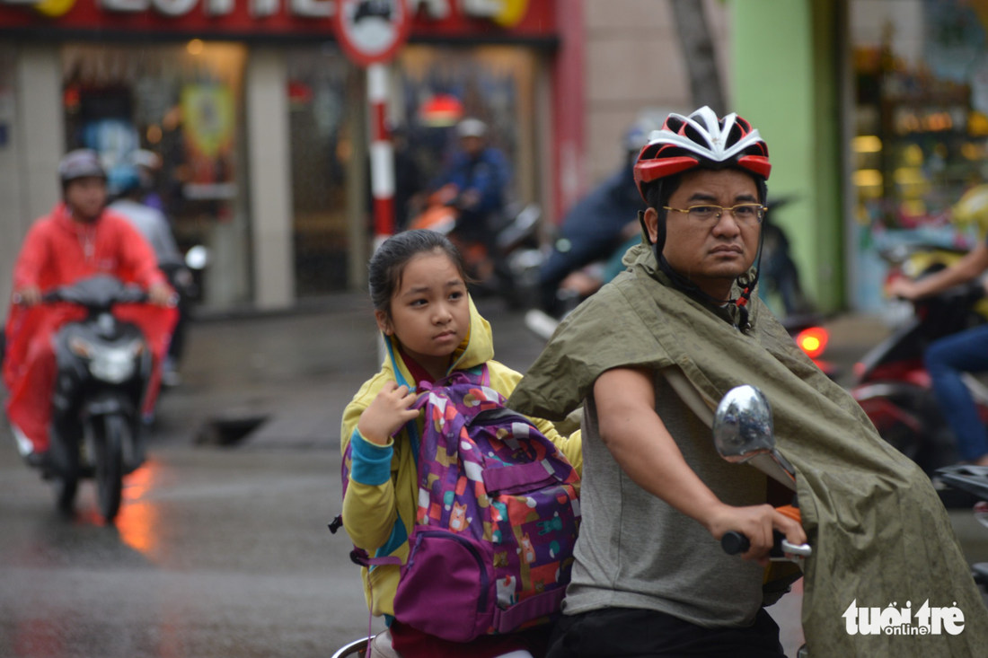 A father takes his daughter home in the rain in Ho Chi Minh City on December 25, 2017. Photo: Tuoi Tre