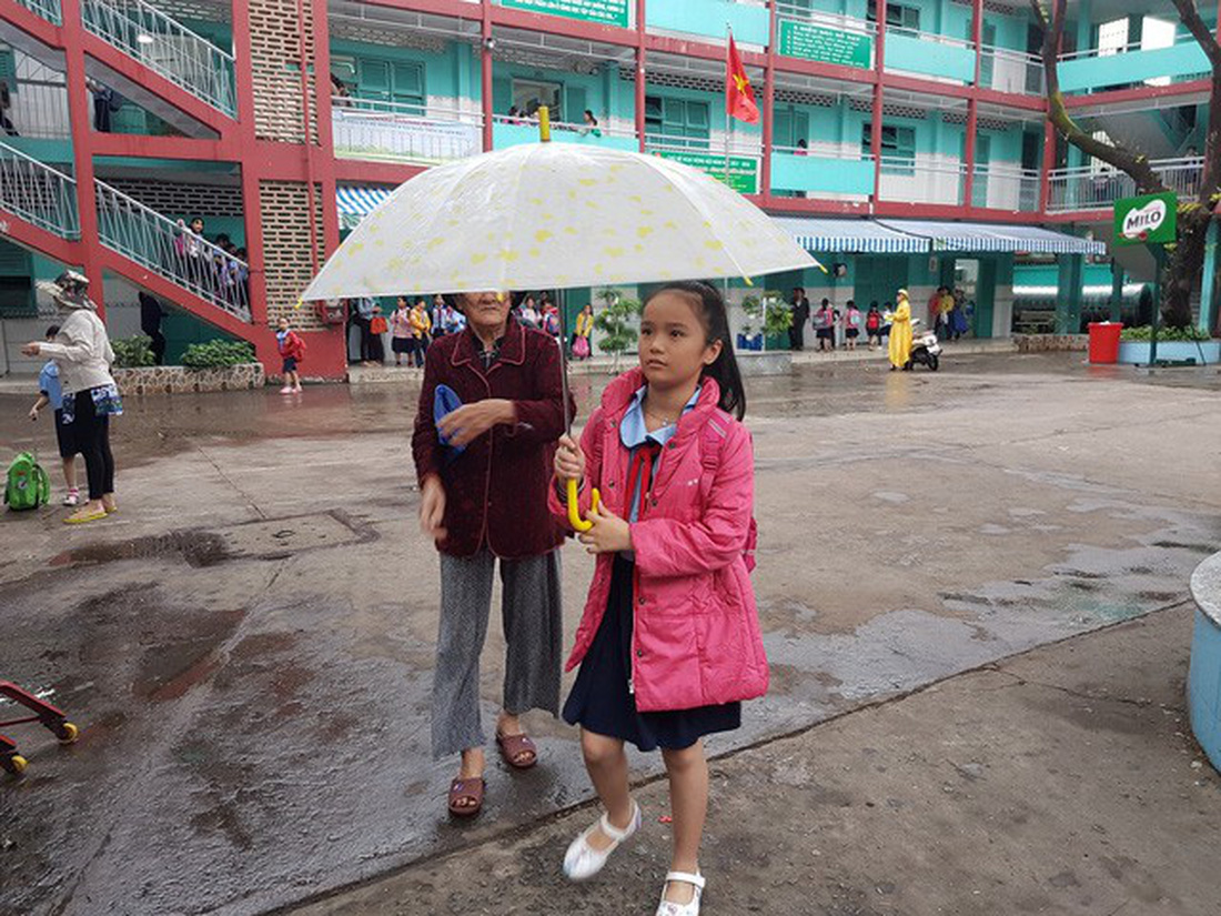 A mother takes her daughter home in the rain in Ho Chi Minh City on December 25, 2017. Photo: Tuoi Tre