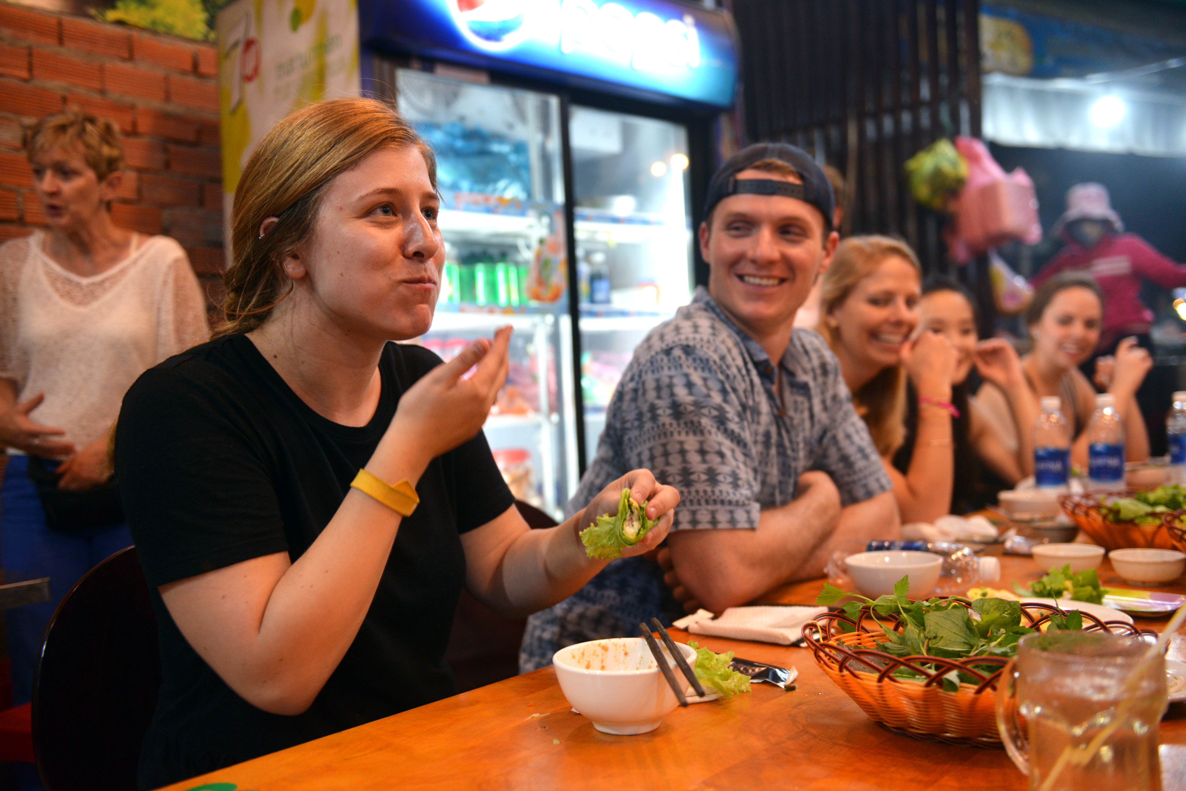 Zachary Devaney (L, 2nd) laughs when his friends try Vietnamese bánh xèo at a small restaurant in District 3, Ho Chi Minh City on December 29, 2017. Photo: Tuoi Tre