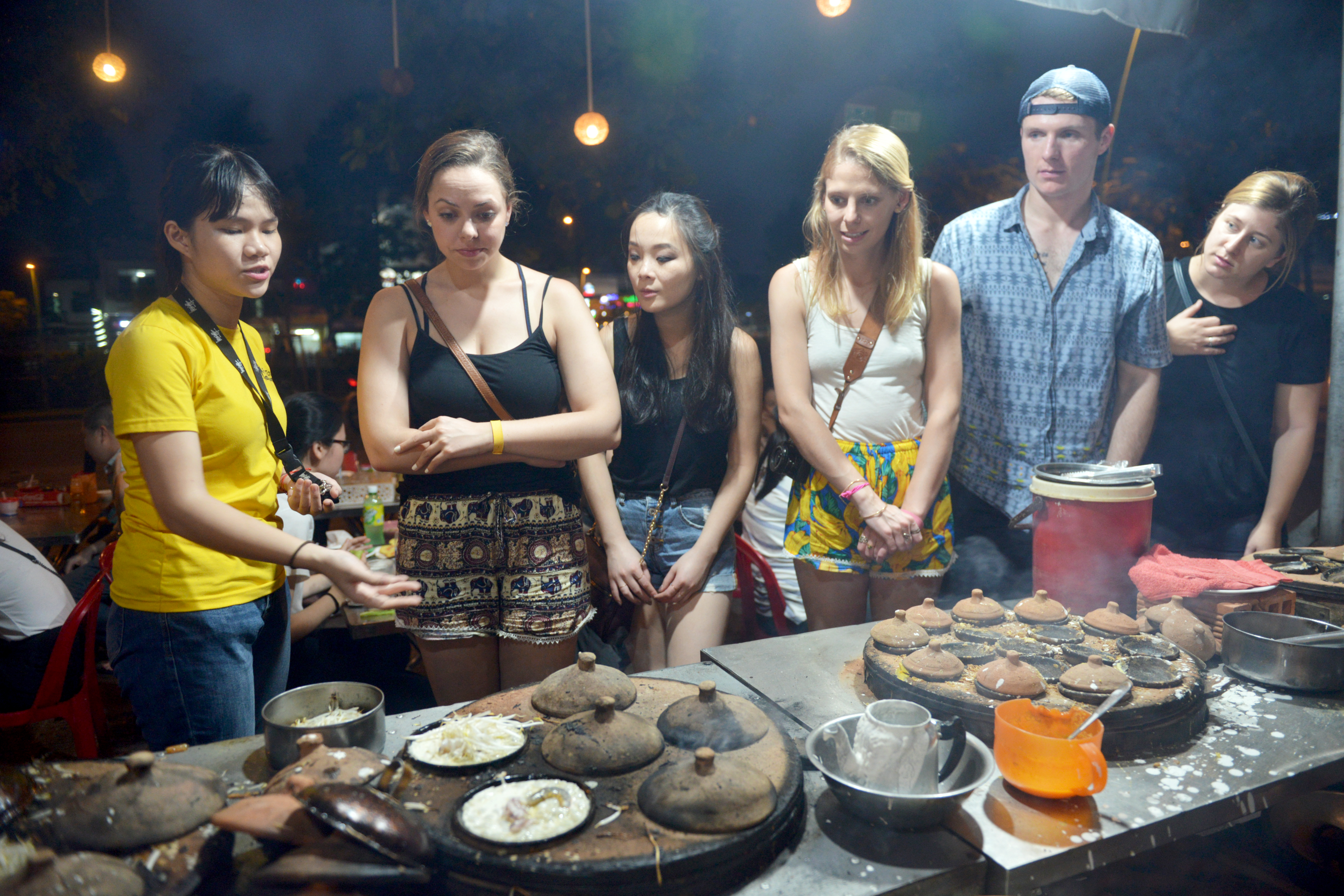 Madeline Dickson (L, 2nd) and her friends watch the process of making Vietnamese bánh xèo at a small restaurant in District 3, Ho Chi Minh City on December 29, 2017. Photo: Tuoi Tre