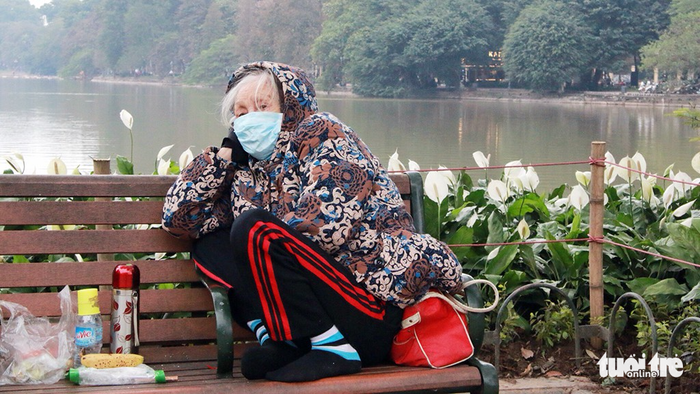 An elderly woman curls up on a bench alongside Ho Guom (Sword Lake) in Hanoi on January 9, 2018. Photo: Tuoi Tre