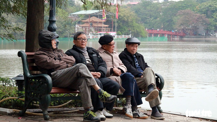 Senior citizens sit by the Sword Lake.
