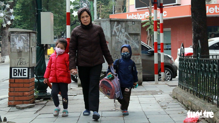 A woman walks her two children to school.