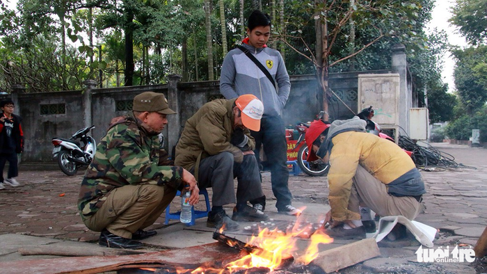 A group of motorbike taxi drivers sit by a bonfire on Kim Ma Street.