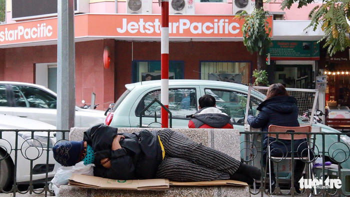 A homeless person sleeps on a bench on a sidewalk.