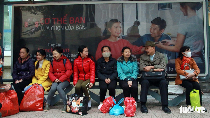 People endure the cold as they wait for a bus.