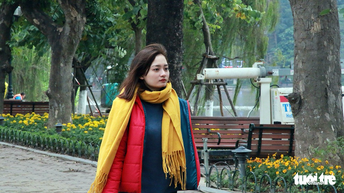 A woman wears jackets and woolen scarves amidst the cold air.