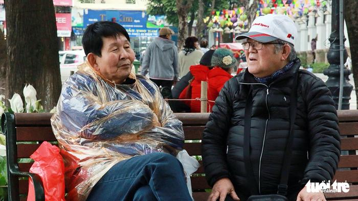 An elderly woman puts on a rain poncho.
