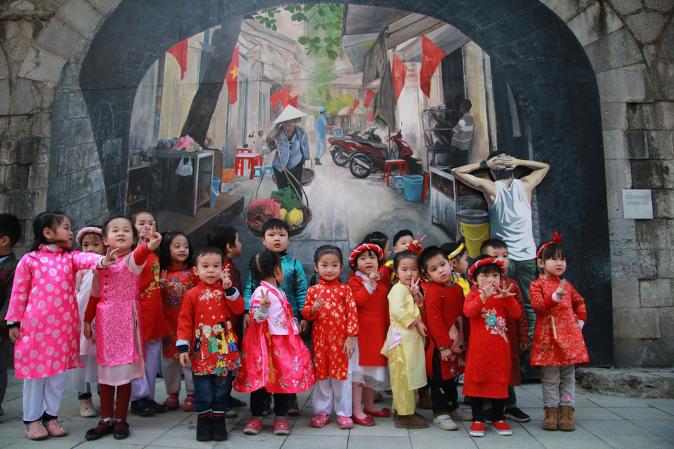 Children in red, a theme color of Tet, pose for photos with a vendor fresco in the background. Photo: Tuoi Tre
