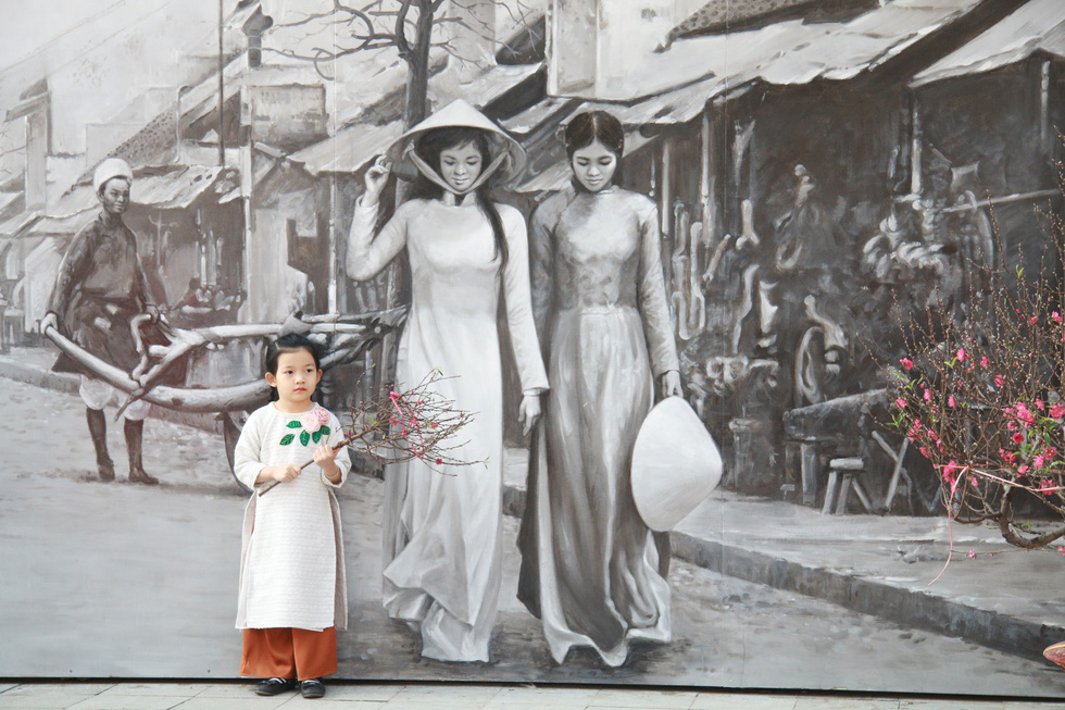 A black-and-white fresco of Vietnamese women in ao dai, the country's traditional national outfit. Photo: Tuoi Tre
