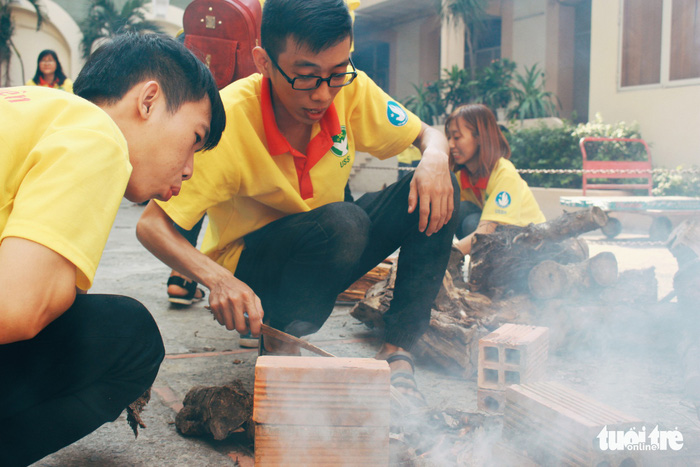"A number of young volunteers were puzzled with the wooden kindling. ""This is the first time we've had to kindle a fire. It felt like ""the olden days"" of our ancestors,"" Nguyen Gia Bao (19, volunteer) said. Photo: Tuoi Tre"