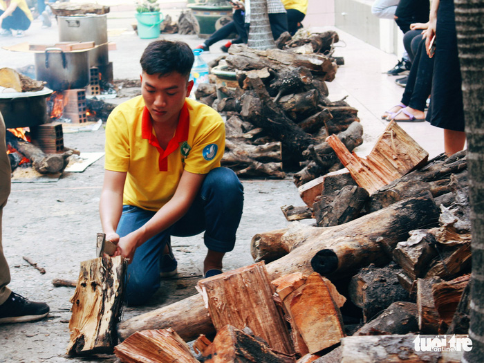 A volunteer chops wood to boil water for steaming the cakes. Photo: Tuoi Tre
